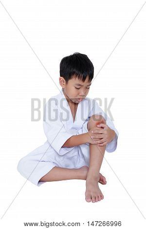 Child athletes taekwondo Injured. Asian handsome boy looking at wound on his knee isolated on white background. Sad boy sitting at studio. Concept of sport physical accident and sport injury.