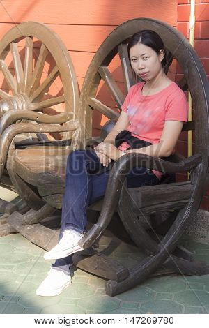 Thai Woman sitting on the cartwheel chair