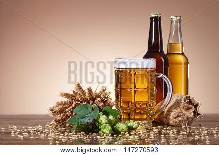 Assortment of fresh beer in bottles, ears of wheat, ripe fruit hops, with beer mug, brewing ingredients, a glass bottle with a drink, a wooden table, bag of ripe grain