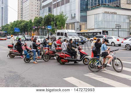 CHENGDU CHINA - MAY 8 2016: Bicyclists and bikers on the street in Beijing China. Bicycles are a common form of transportation in the country.