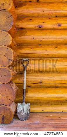 Garden spade photo against wooden wall in the corner