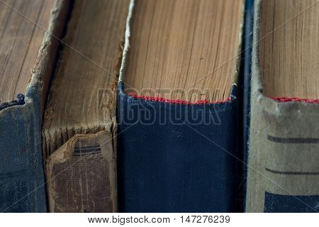 Vintage antiquarian tattered books close up. Selective focus