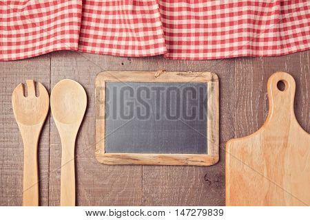 Abstract wooden background with red checked tablecloth chalkboard and kitchen utencils. View from above