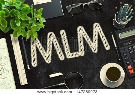 MLM - Text on Black Chalkboard.3d Rendering. Toned Illustration.