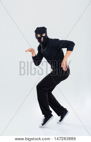 Funny scared criminal young man in balaclava running out