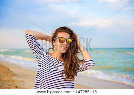 summer holidays and vacation concept happy girl in striped dress standing on the ocean or sea beach with copy space horizontal shot. Portrait of woman with hair in the wind posing on the beach.