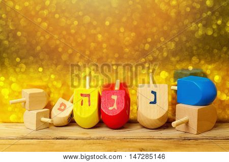 Jewish holiday Hanukkah background with spinning top dreidel on wooden table over golden bokeh