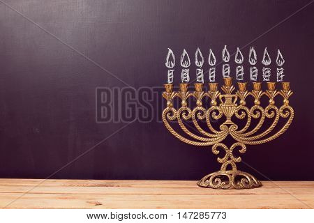 Jewish holiday Hanukkah background with menorah over chalkboard with hand drawing