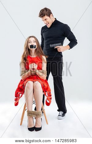 Cruel angry man threatening scared woman by gun isolated on the white background
