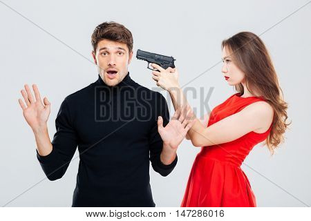 Beautiful young woman standing and threatening with gun to scared young man