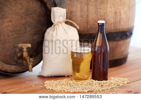 brewery, drinks and alcohol concept - close up of old beer barrel, glass, bottle and bag with malt on wooden table
