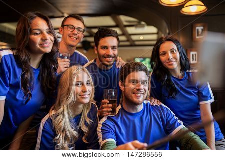 people, leisure, friendship and technology concept - happy friends or football fans taking picture by smartphone selfie stick and drinking beer at sport at bar or pub