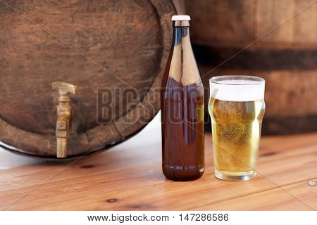 brewery, drinks and alcohol concept - close up of old beer barrel, glass and bottle on wooden table
