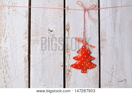Christmas tree ornament hanging over white wooden background