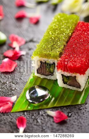 Tobiko Spicy Maki Sushi - Hot Roll Topped with various type of Tobiko (flying fish roe). Tuna, Cucumber and Green Lettuce inside. Served on Banana Leaf with Flowers
