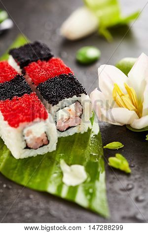 Chess Maki Sushi - Roll with Prawn and Feta Cheese inside. Topped with Black and Red Tobiko (flying fish roe). Served on Banana Leaf with Flowers