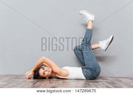Portrait of a smiling attractive woman lying on the floor with raised legs on gray background