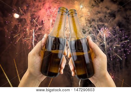 hands raised toasting with beer and fireworks on the background for the new year