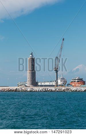 White Sailboat in the Sea and Crane at Work in Boatyard near Lighthouse