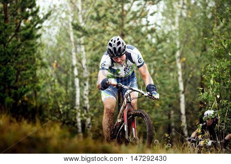 Revda Russia - July 31 2016: girl athlete mountainbiker heavy uphill in forestduring Regional competitions on cross-country bike