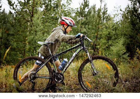 Revda Russia - July 31 2016: teen boy athlete uphill on foot with his bicycle during Regional competitions on cross-country bike