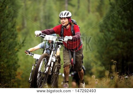Revda Russia - July 31 2016: group of athlete mountainbikers climb a steep hill in forest during Regional competitions on cross-country bike