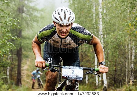 Revda Russia - July 31 2016: closeup of a male cyclist rides through forest he has a dirty face during Regional competitions on cross-country bike