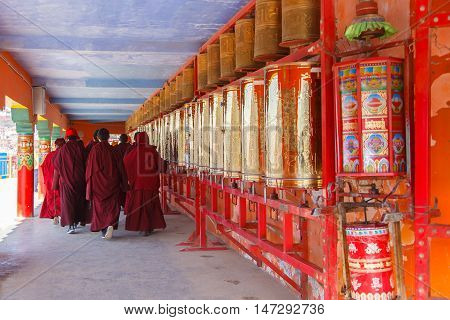 Buddhist nun walking touch a prayer wheels around the sanctuary at Larung gar (Buddhist Academy) in Sichuan China
