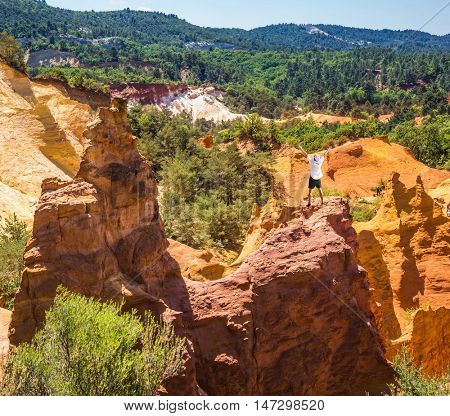 Orange and red picturesque hills in Roussillon. Elderly man admires a magnificent landscape