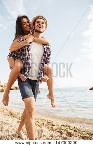 Handsome smiling young man giving piggy back ride to his girlfriend at the beach