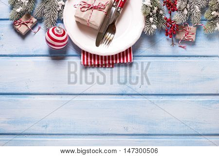 Christmas table setting. White plate knife and fork napkin and christmas decorations in white and red colors on blue wooden table. Top view. Selective focus. Place for text.
