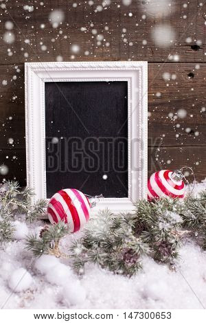 Empty blackboard christmas balls and branches fur tree on aged wooden background. Drawn snow. Decorative christmas composition. Selective focus. Place for text.