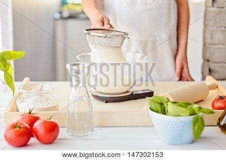 Woman Sifting Flour Through Sieve.