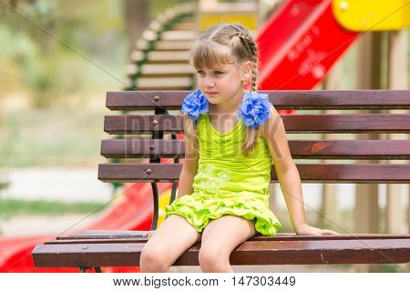 Portrait Of Upset Five Year Old Girl Who Is Sitting On The Bench On The Background Of The Playground