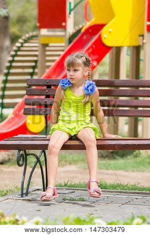 Upset Girl Sitting On The Bench On The Background Of The Playground