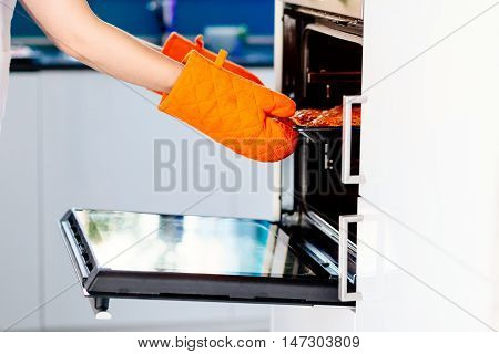 Woman Pulling A Pizza From Electric Oven