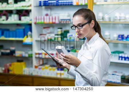 Pharmacist using digital tablet while checking medicine in pharmacy