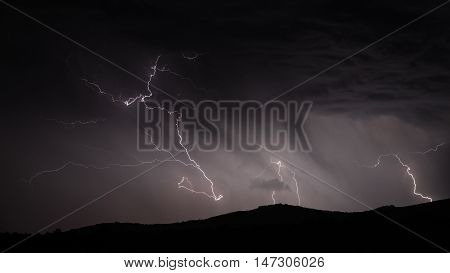 Closeup view of Lightning strike over mountain range