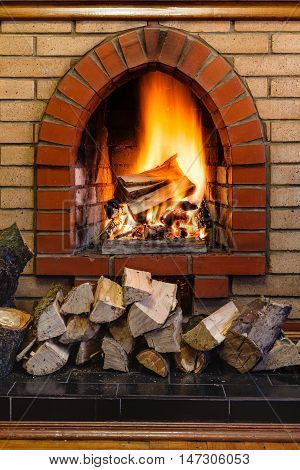 Wood Logs And Fire In Indoor Brick Fireplace