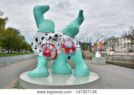 Hanover, Germany - April 18, 2016. Nana sculptures Caroline and Sophie in the background by French artist Niki de Saint Phalle, on Leibnizufer in Hanover, with trees and surrounding buildings.