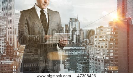 Double exposure image of a modern businessman with digital tablet over a city view. Business man with modern tablet with skyskrapers in background during the morning sunlight. New technology concept.