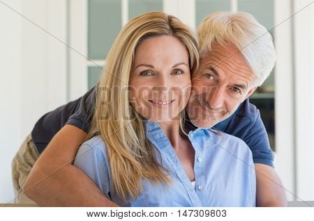 Portrait of a senior smiling couple looking at camera. Senior man embracing behind his wife. Happy smiling retired couple in love.