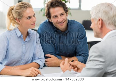 Businessman explaining loan policy to young couple. Happy couple discussing with a financial agent their new investment. Financial consultant presents bank investments to a smiling woman and her man. poster