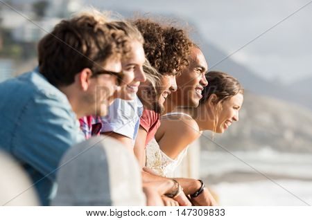 Group of smiling friends leaning over fence while looking at sunset. Happy young women and men in a row looking the sunset over the ocean. Young people enjoying view and contemplating.