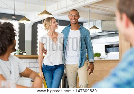 Happy cheerful african man introducing his beautiful girlfriend to his friends. Happy friends meeting over weekend to enjoy. Happy guys wating their couple friend at cooffe shop.