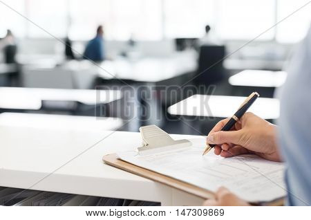 Close up hands of a business woman filling in recruitment form. Business woman making notes on clipboard. Hands of a young woman signing the sheet.