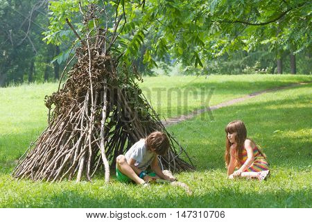 kids playing next to wooden stick house looking like indian hut, tepee