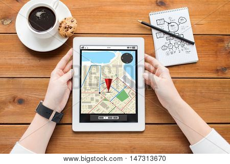 business, location, education, technology and people concept - close up of woman with gps navigator map on tablet pc computer screen and coffee on wooden table with gps navigator map on screen