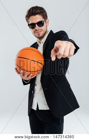 Smiling handsome man in sunglasses and black suit holding basket ball and pointing finger at camera over grey background