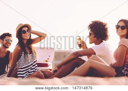 Spending nice time with friends. Cheerful young people spending nice time together while sitting on the beach and drinking beer